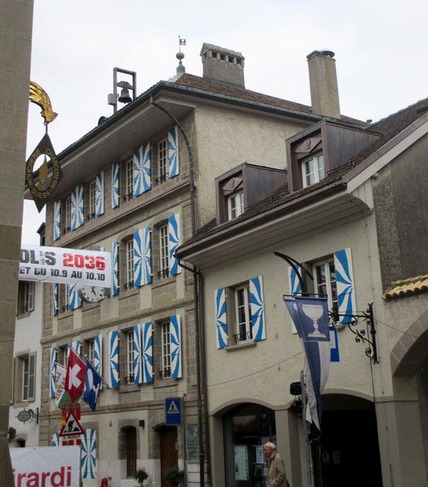 Foto Der Durchgang zum Innenhof des Maison de Ville an der Grand Rue 65. Die Altstadt ist aus Anlass des Fêtes des Bourg beflaggt