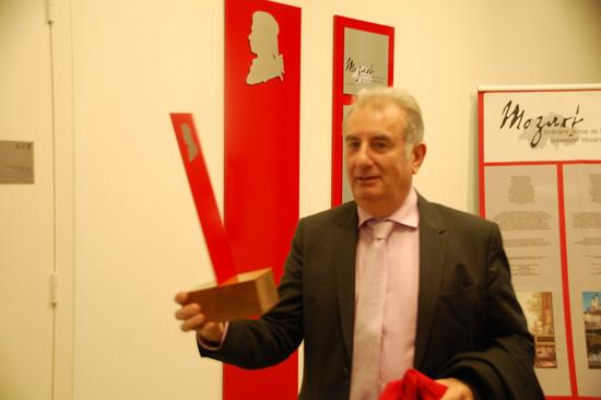 Photo Hervé Klopfenstein, directeur général, avec la petite stèle devant la grande stèle qui orne le mur du hall d'entré