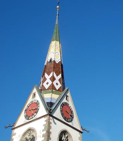 Foto Der farbige Kirchturm der Kirche von Schleitheim. Er beherbergt als kleinste Glocke das von 1608 stammende sogenannte Chriesiglöggli